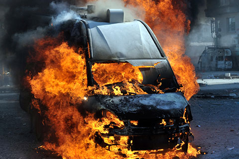 a black van explodes into flames in the street